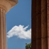 Blue sky with a white cloud and doric columns. 5 column approach