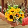 A bouquet of sunflowers, leaves and white flowers passed from one hand to another