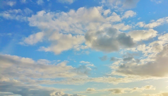 Sensory Overload Photograph of blue sky with white fluffy clouds.