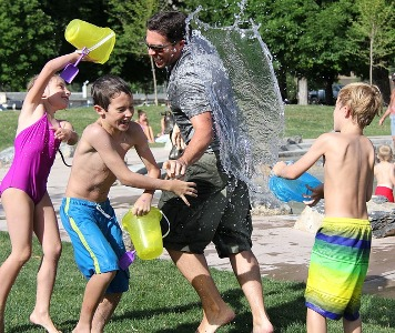 Sensory Overload. Photo of man and 3 boys with coloured buckets throwing water