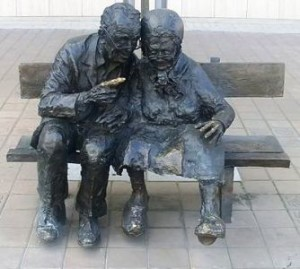 Intimacy Sex and Brain Injury. Bronze statue of older man and woman together on seat