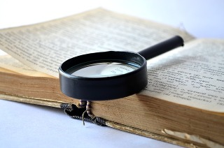 Old dictionary with magnifying glass on the open page