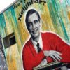 Mr Rogers Mural of Mr Rogers wearing red cardigan on side of building