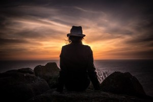Sensory overload Photo person wearing a hat sitting on rocks watching sunset